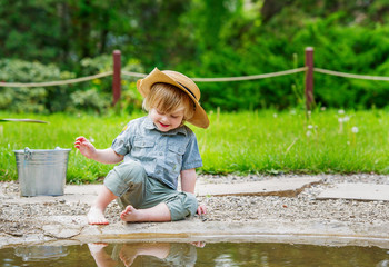 Very happy kid in straw hat by the pond