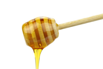Honey dripping from wood honey spoon