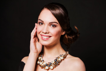 smiling brunette with makeup wearing jewelry