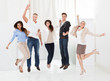 Confident Businesspeople Jumping With Arms Raised