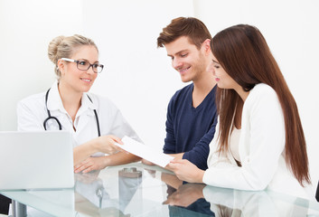Doctor Giving Prescription Paper To Couple