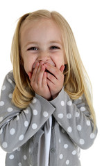 Cute blond girl laughing with her hands to her mouth