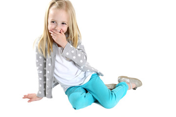 cute blond girl sitting hand to mouth laughing