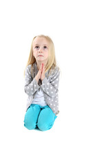 adorable young girl kneeling in prayer looking up