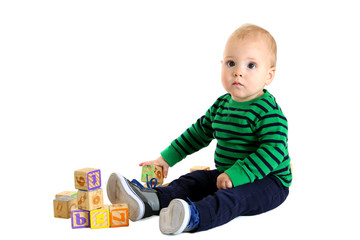 Cute young toddler boy playing with aphabet blocks