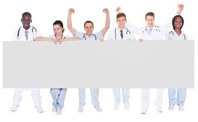 Confident Doctors Holding Blank Billboard