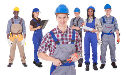 Engineer Holding Tool With Team Against White Background