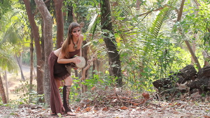 Girl with a drum in the jungle.
