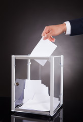 Businessman Inserting Ballot In Box On Desk
