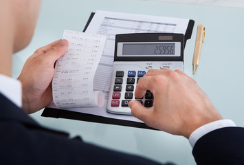 Businessman Holding Receipt While Calculating Expense In Office