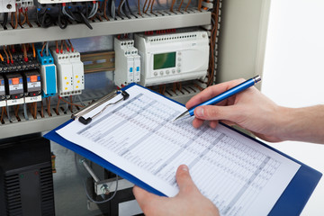 Electrician Holding Clipboard While Examining Fusebox