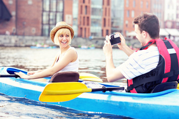 Happy tourists taking pictures in a canoe
