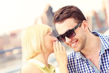 Woman whispering to boyfriend