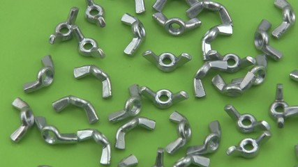 Chrome wing nuts rotating on a green  background.