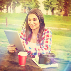 Young tourist woman with tablet in park