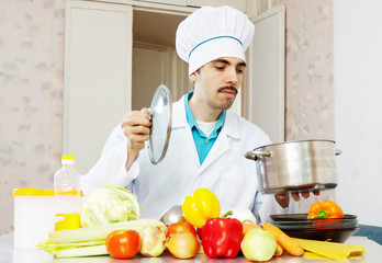Male cook in uniform cooking with vegetables