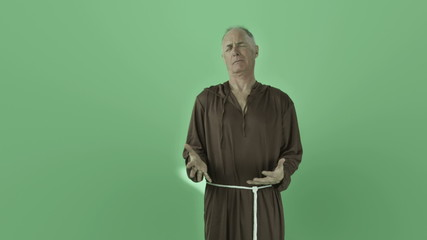 Senior caucasian monk isolated on chroma green screen anger