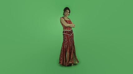 woman in traditiona indian outfit isolated on green confident