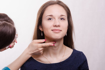 Beautiful model makeup artist applied concealer on neck