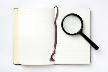 Open notebook with magnifying glass on white background. Search