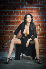 Sexy brunette in black sitting in front of red brick wall