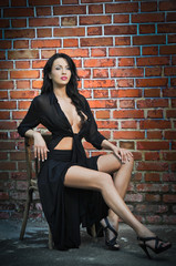 Sexy brunette woman in black sitting in front of brick wall