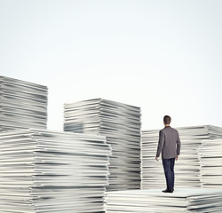 businessman standing on a pile of blank documents