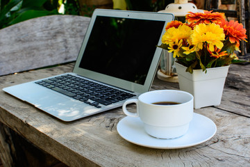coffee, laptop on wood floor with flower