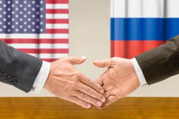 Vertreter der USA und Russlands reichen sich die Hand