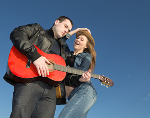 Young couple playing acoustic guitar and dancing