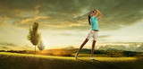 Fototapety Woman golfer hitting the ball on the  scenery  beautiful