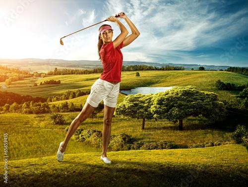 Fototapeta Woman golfer hitting the ball on the scenery beautiful