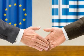 Vertreter der EU und Griechenlands reichen sich die Hand