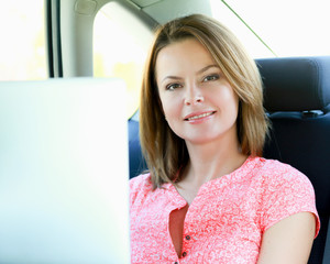 business travel: busy businesswoman with laptop in car
