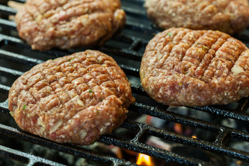 Raw burgers on barbecue grill with fire