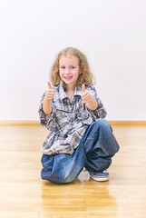 Smiling little girl in oversized jeans and shirt.