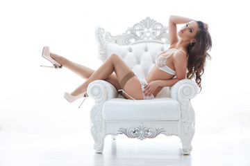 Beautiful alluring young woman in sexy lingerie sitting in luxur