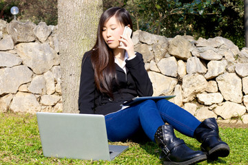 Asian young business woman working with technology in park