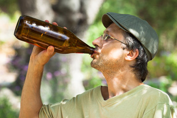 Man drinking beer from bottle outdoors