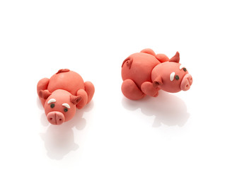 two pig doll from clay on white background