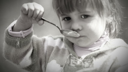 Black and White portrait : Cute Little girl eats with spoon