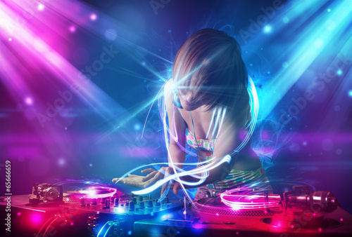 Energetic Dj girl mixing music with powerful light effects