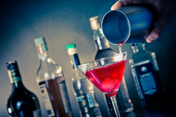 Barman pouring a red cocktail into a glass with ice