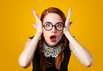 Surprised redhead girl on yellow background.