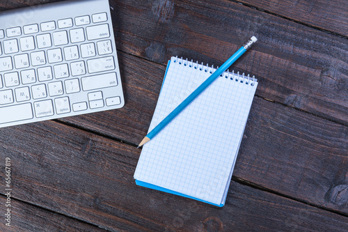 Keyboard, notebook and pencil on wooden table.