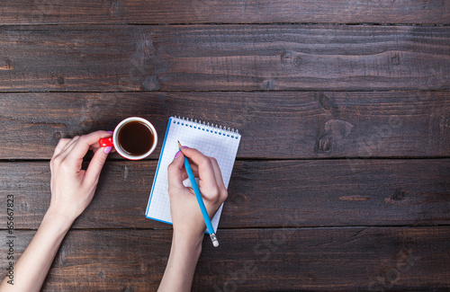 Hands holding notebook and coffee cup.