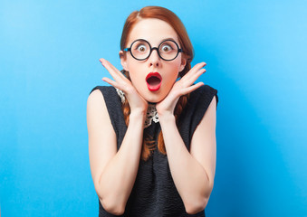 Surprised redhead girl on blue background.