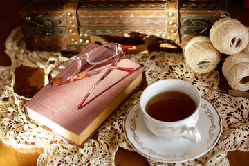 Romantic composition of tea cup, book and glasses on table.