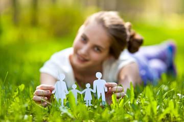Крупным планом девушка держит в руках бумажную семью