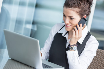 Young Businesswoman with Computer and Mobile Phone